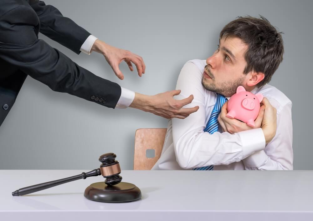 Mężczyzna trzyma świnkę z oszczędnościami, ale zgodnie z prawem musi oddać pieniądze, bo ma długi.